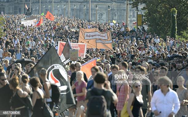 Antiracism protesters hold a banner reading Refugees welcome during a rally on August 29 2015 in Dresden stronghold of the antiIslam PEGIDA movement...
