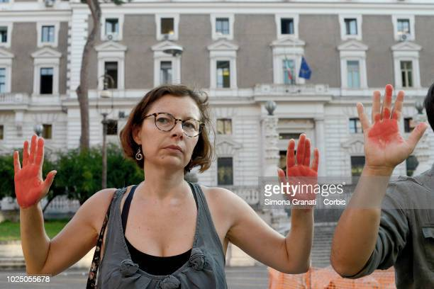 Antiracism protesters with hands marked red to symbolise the blood of migrants who have died at sea demonstrate in front of the Viminale the seat of...