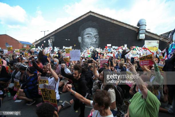 Anti-racism protestors demonstrate by a mural of England forward Marcus Rashford after it was defaced on July 13, 2021 in Manchester, northwest...