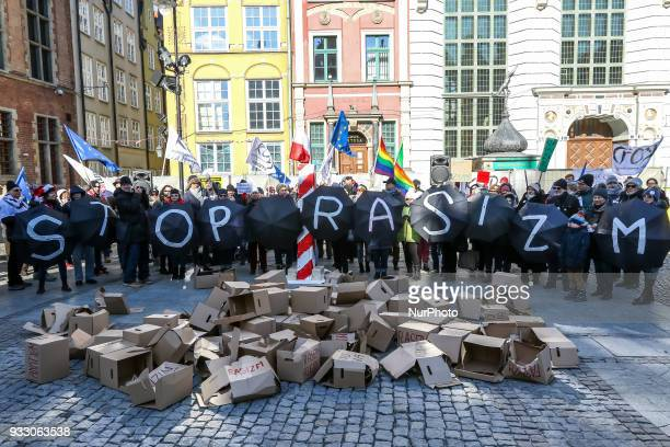 Antiracist demonstration participants holding umbrellas with STOP RACISM inscription are seen in Gdansk Poland on 17 March 2018 People gather in the...