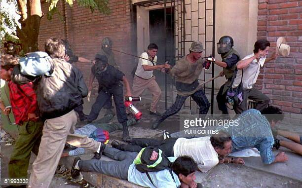 Antiriot police and excombatants clash outside a government office 23 November in San Salvador after the police stormed the buildiong to free 27...