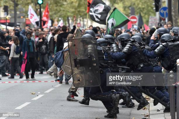 TOPSHOT Antiriot police charge protesters on the sidelines of a demonstration on October 10 2017 in Paris part of a nationwide strikes and...