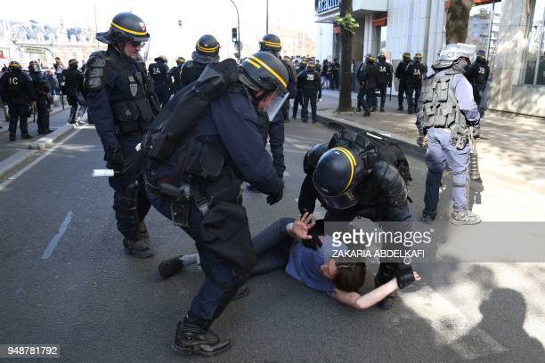 CRS antiriot police detain a man during clashes at a demonstration on April 19 in Paris as part of a multi branch day of protest called by French...