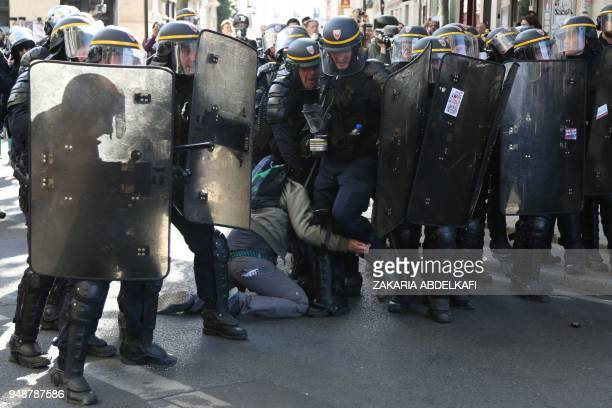 TOPSHOT Antiriot police detain a protester during a demonstration on April 19 in Paris as part of a multi branch day of protest called by French...