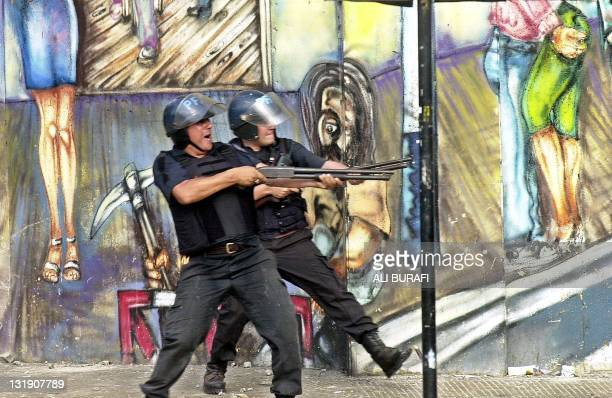 Antiriot police fire their rifles in the direction of demonstrators during protests against the government of Argentine President Fernando de la Rua...