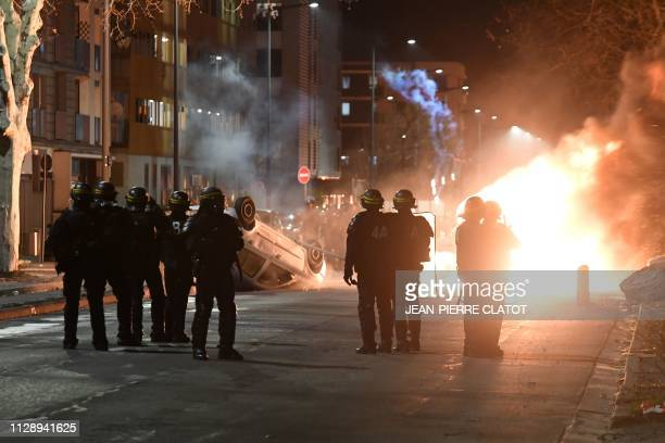 TOPSHOT Antiriot police hold a position as cars are set on fire in a street of Grenoble centraleastern France on March 6 on the fourth night of...
