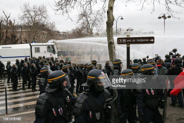 Antiriot police members spray water on demonstrators near the Arc de Triomphe during an antigovernment demonstration called by the Yellow Vests...