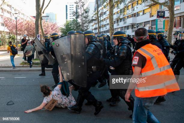 TOPSHOT Antiriot police officers crush a protester during clashes on the sidelines of a demonstration on April 19 2018 in Paris as part of a multi...