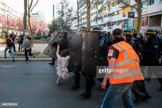 Antiriot police officers crush a protesting woman during clashes on the sidelines of a demonstration on April 19 2018 in Paris as part of a multi...