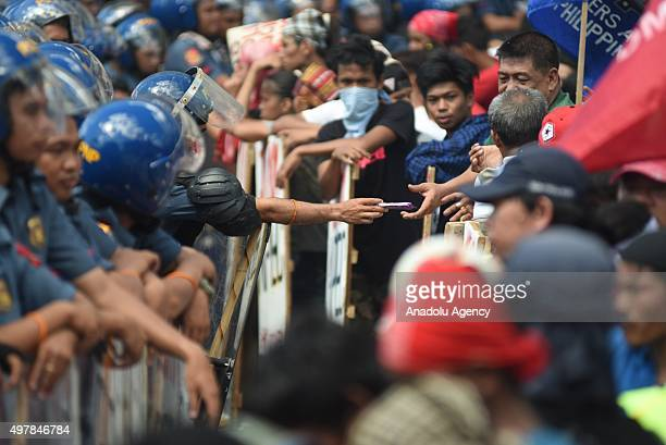 Antiriot police officers offer food to activists as protesters from various groups attempt to march towards the venue of the Asia Pacific Economic...