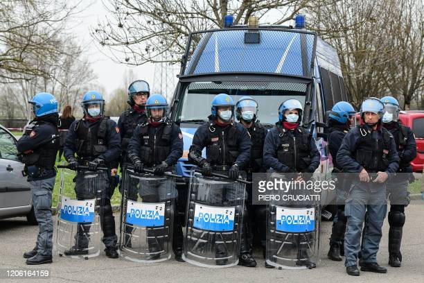 Antiriot police officers some wearing a protective respiratory mask stand guard following a revolt of prisoners against measures including a ban on...