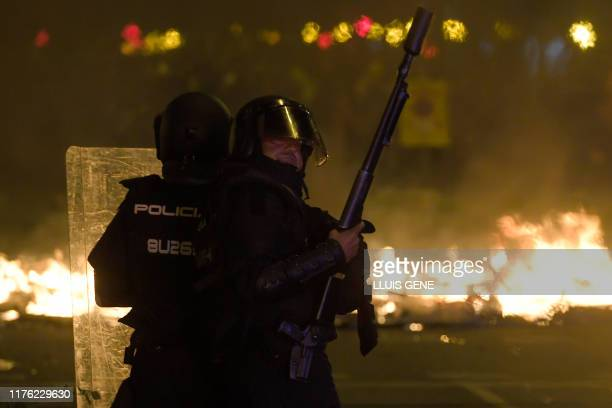 Antiriot police officers stand guard in front of a barricade in flames during a demonstration called by the local Republic Defence Committees in...