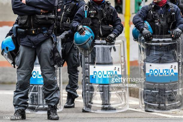 Anti-riot police officers stand guard outside the San Vittore prison in Milan as inmates stage a protest on a rooftop of a wing at the prison on...