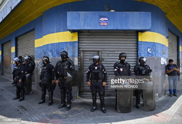 Anti-riot police stand guard outside shops and supermarkets in San Salvador on March 30, 2020 during a protest against the closure of the offices...