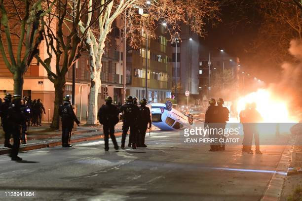 Antiriot police take position as cars are set on fire in a street of Grenoble centraleastern France on March 6 on the fourth night of violence...