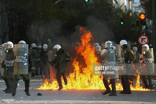 Antiriot police try to avoid a molotov cocktail thrown by protestors during a demonstration in Athens on December 18 2008 The Greek capital was...