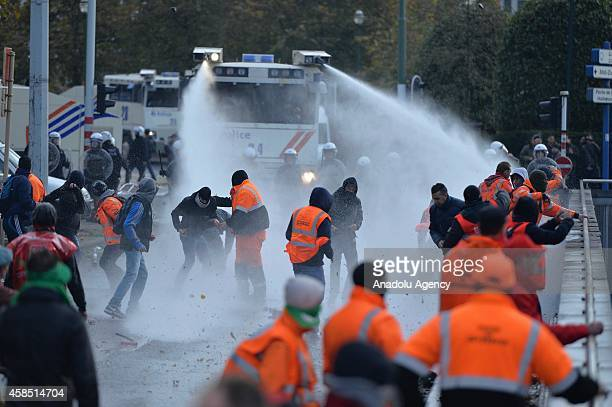 Antiriot police use water cannon to disperse demonstrators protesting against the government's austerity policies in Brussels Belgium on November 6...