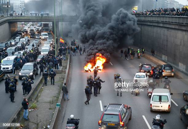 TOPSHOT Antiriot policemen arrive as taxi drivers block the traffic with a fire during a demonstration against the VTC on January 26 2016 on the...