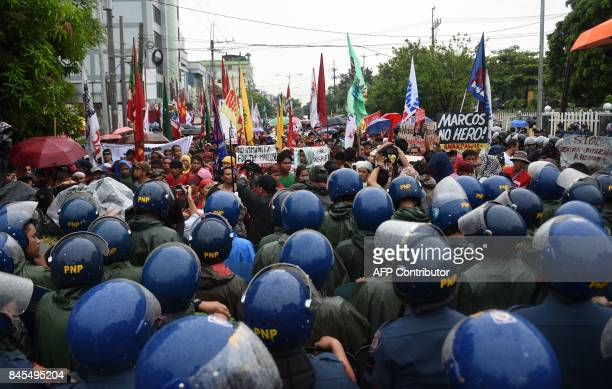 TOPSHOT Antiriot policemen block antiMarcos protesters during a demonstration held on the 100th birthday of late dictator Ferdinand Marcos near the...