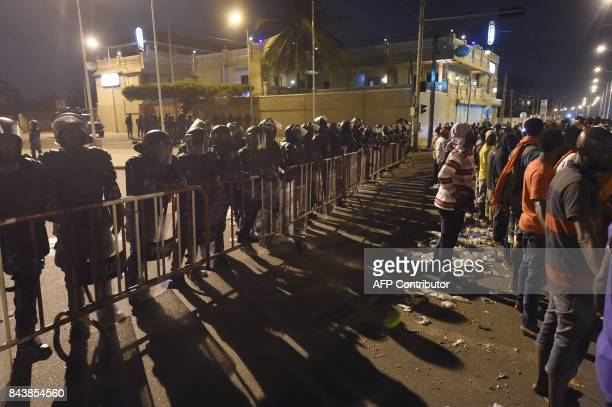 Anti-riot policemen block the road against opposition supporters keeping an all-night vigil to press for constitutional reform, during...