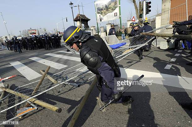Antiriot policemen clean a roadblock on April 2 2009 in Strasbourg eastern France after an antiNATO demonstration held son the eve of Strasbourg and...