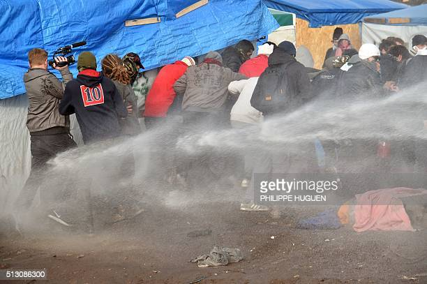 TOPSHOT Antiriot policemen spray water on migrants and refugees to disperse them during the dismantling of half of the 'Jungle' migrant camp in the...