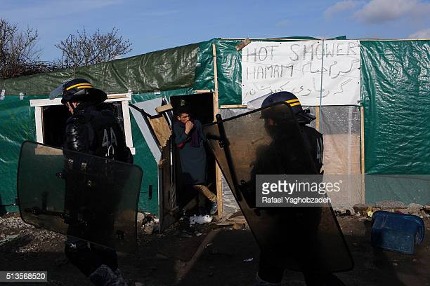 Antiriot policemen walk in front of makeshift showers inside the 'Jungle' migrant camps in the French northern port city of Calais as agents...