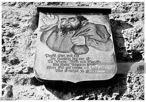 Medieval inscription on the town wall, Rothenburg, Germany, . The placard shows a jew with a money bag. The text reads: Making big profits, greed and...