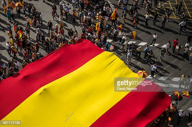Antiseparatist Catalans hold a huge spanish flag during a demonstration on October 12 2014 in Barcelona Spain According to the Barcelona Metropolitan...