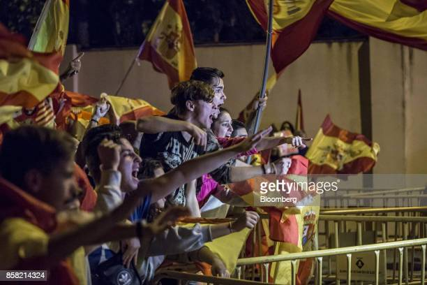 Antiseparatist demonstrators in support of the Spanish National Police and Civil Guard wave Spanish national flags during a protest near a Civil...