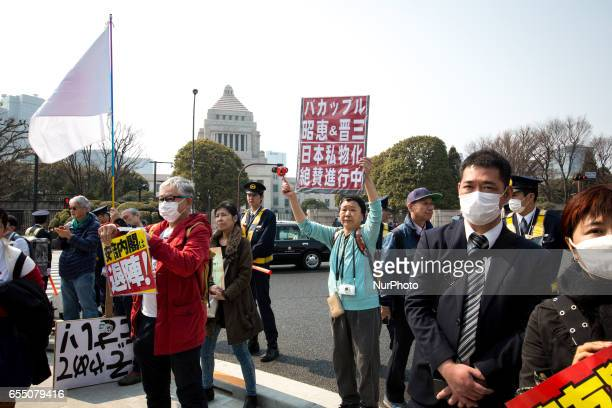 AntiShinzo Abe protesters holds a placards in front of Tokyo parliament during a rally denouncing his government policies and calling on the Japanese...