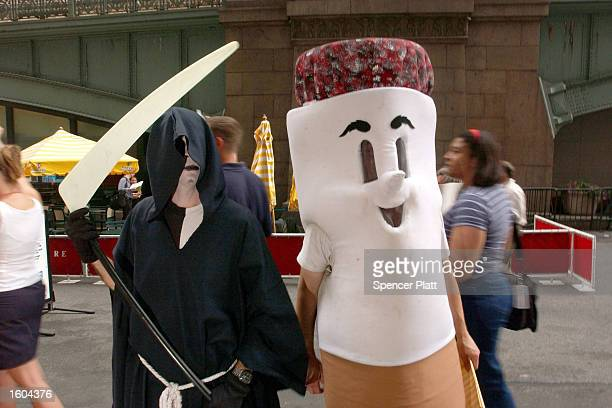 Antismoking demonstrators dressed as the grim reaper and a cigarette protest in front of the Philip Morris company''s headquarters July 25 2001 in...