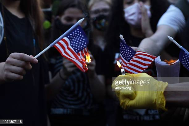 Anti-Trump activists burn U.S. Flags at Black Lives Matter Plaza near the White House July 4, 2020 in Washington, DC. Anti-Trump activists rallied on...