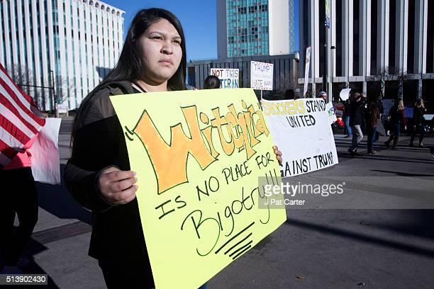 AntiTrump protester stands outside the convention center where Republican presidential candidate Donald Trump made a speech at a campaign rally on...