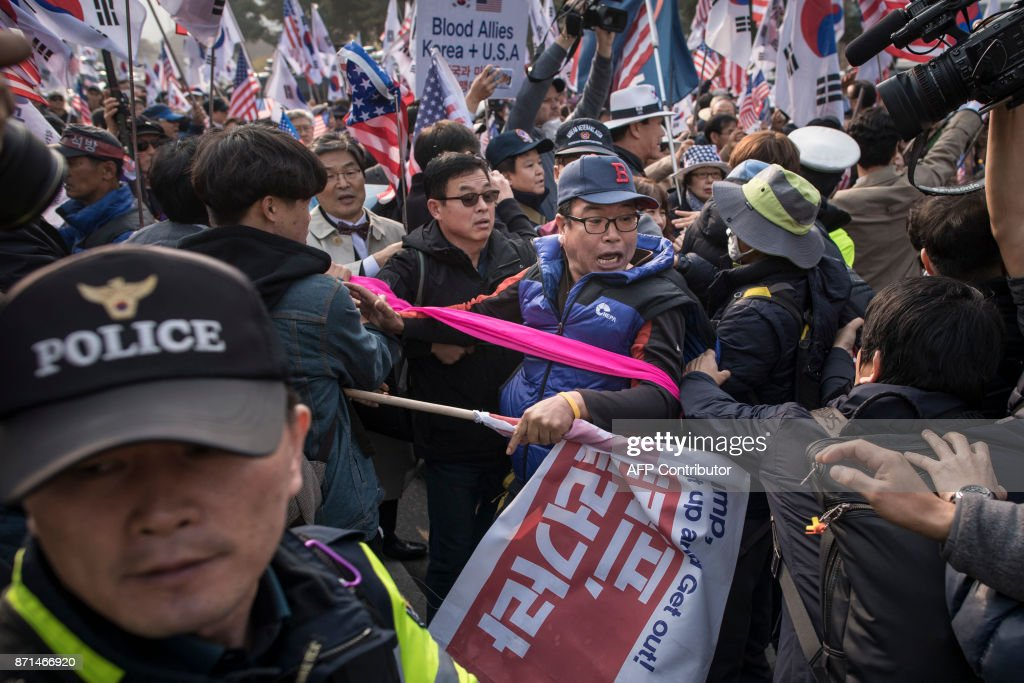 Anti-Trump protesters attempt to stop US/Trump supporters from entering their rally outside the National Assembly in Seoul on November 8, 2017. US President Donald Trump offered North Korean leader Kim Jong-Un what he called 'a path towards a much better future' as tensions soar over Pyongyang's nuclear ambitions. / AFP PHOTO / Ed JONES