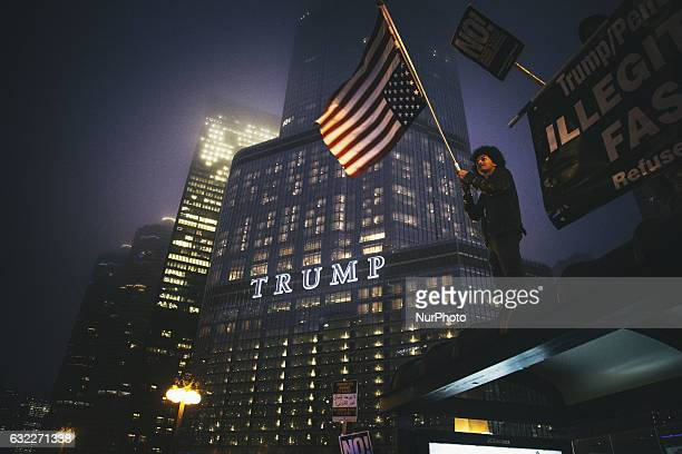 AntiTrump protesters gather atop a car in front of Trump Tower in Chicago during a mass demonstration on Inauguration Day on January 20 2017