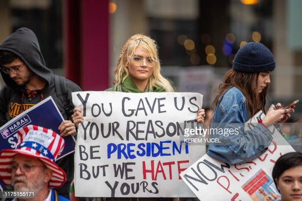 AntiTrump protesters hold signs as they gather outside the Target Center in Minneapolis Minnesota ahead of a Keep America Great rally by the US...
