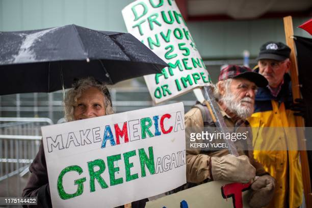 AntiTrump protesters hold signs outside the Target Center in Minneapolis Minnesota ahead of a Keep America Great rally by the US president on October...