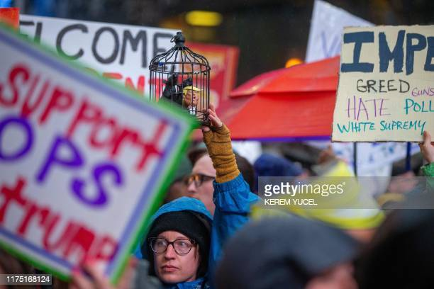 """Anti-Trump protesters hold signs outside the Target Center in Minneapolis, Minnesota, ahead of a """"Keep America Great"""" rally by the US president on..."""