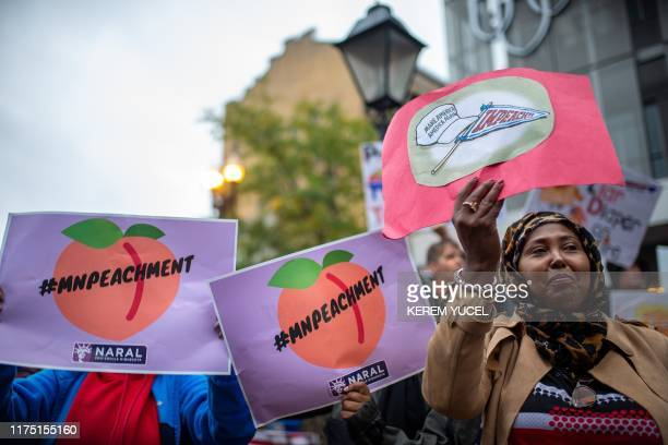 """Anti-Trump protesters hold signs reading """"impeachment"""" as they gather outside the Target Center in Minneapolis, Minnesota, ahead of a """"Keep America..."""