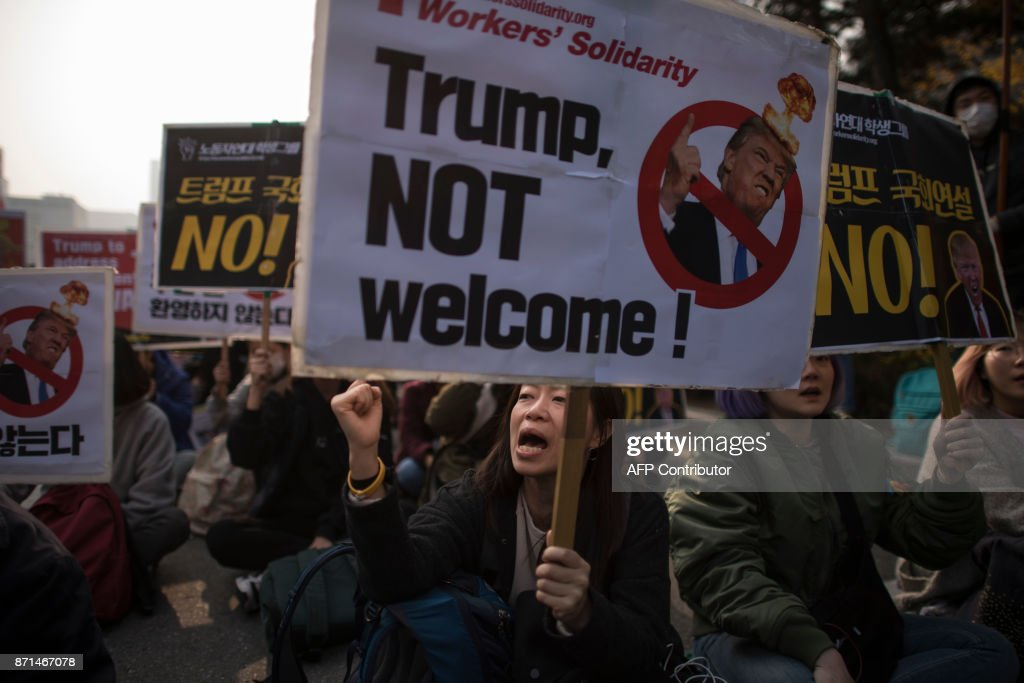 Anti-Trump protesters sshout slogans during a rally outside the National Assembly in Seoul on November 8, 2017. US President Donald Trump offered North Korean leader Kim Jong-Un what he called 'a path towards a much better future' as tensions soar over Pyongyang's nuclear ambitions. / AFP PHOTO / Ed JONES