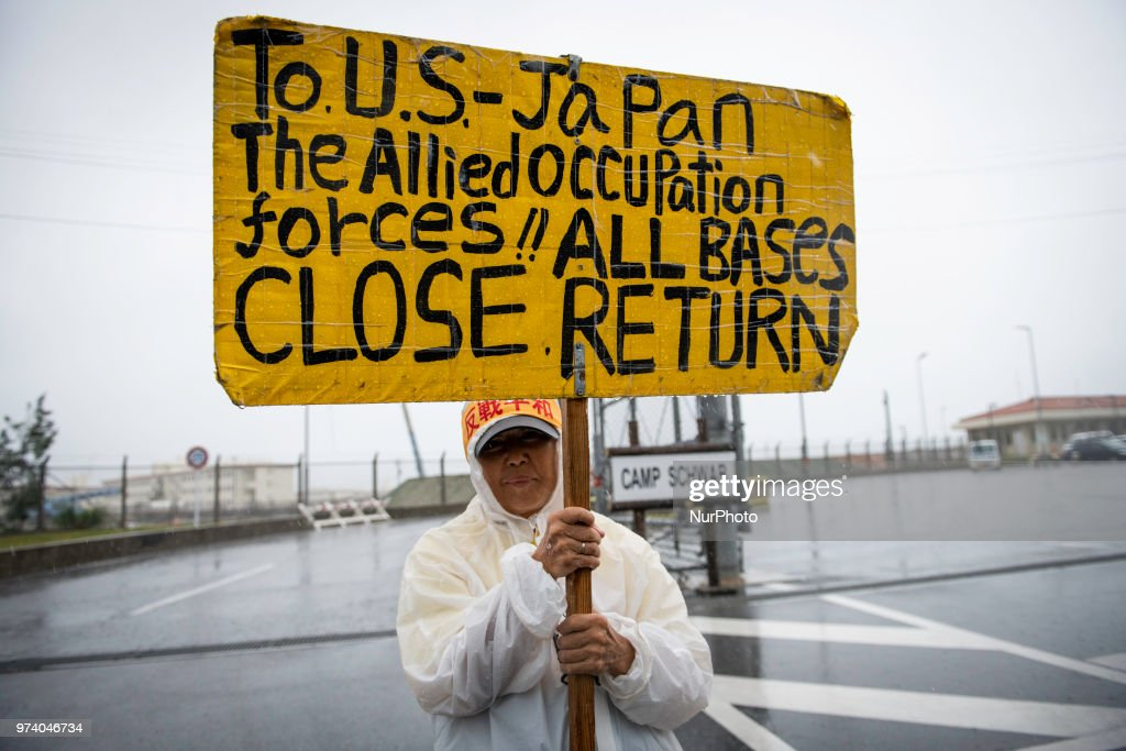 Anti-US base protester holds a placard protesting outside the U.S Base Camp Schwab on June 14, 2018 in Nago, Okinawa prefecture, Japan. Protesters stage a sit-in protest at the gate of the U.S. Marine Corps' Camp Schwab in the Henoko district of Nago blocking the passage of construction vehicles mobilized by the Japanese government for the relocation of the on-going construction of the new U.S Marines Airbase Station in Futenma.