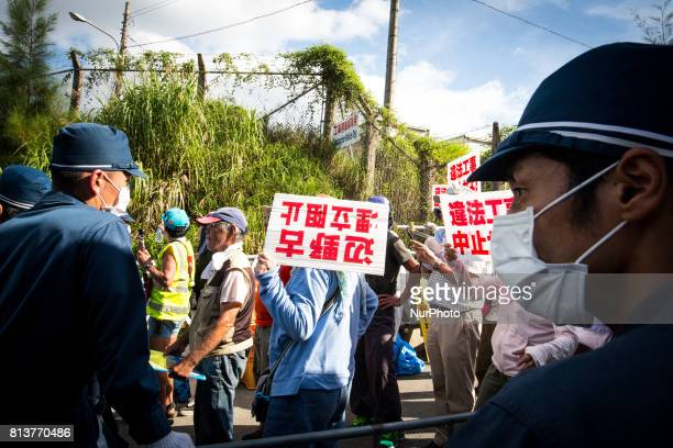 AntiUS base protesters were guarded by riot police as they try to block construction trucks in front of the Camp Schwab gate to protest against the...
