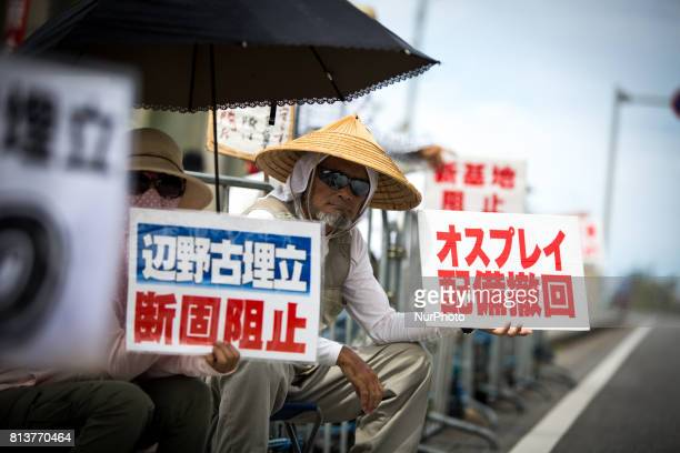 AntiUS base protesters with their placards stage a rally in front of the Camp Schwab gate to protest against the construction of the new US Marine...