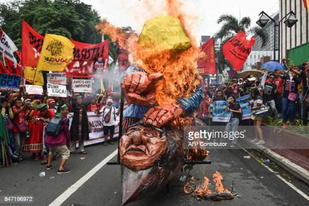 AntiUS protesters burn effigies of US President Donald Trump and Philippine President Rodrigo Duterte during a rally near the US embassy in Manila on...