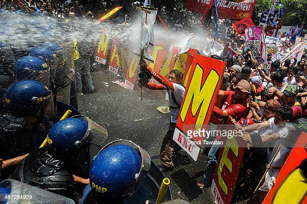 AntiUS protestors clash with riot police using water cannons near the US embassy on April 29 2014 in Manila Philippines US President Barack Obama...