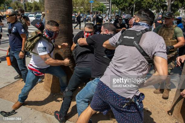 Anti-vaccination protesters beat up a counter protester during an anti-vaccination rally near City Hall following the Los Angeles City Council vote...