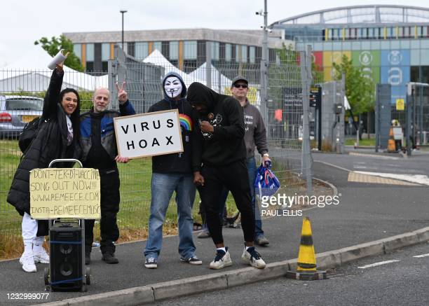 Anti-vaccination protesters stand with placards outside a temporary vaccination centre at the Essa academy in Bolton, northwest England on May 20,...