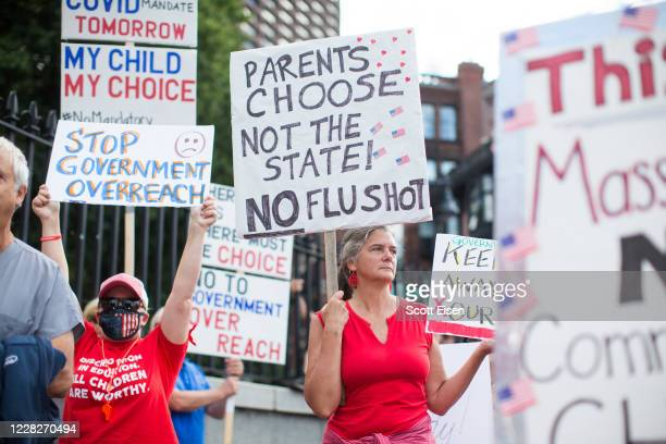 Anti-vaccine activists hold signs in front of the Massachusetts State House during a protest against Governor Charlie Baker's mandate that all...