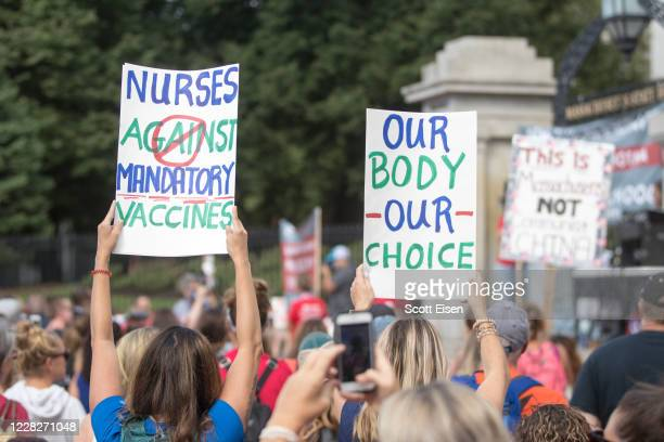 Anti-vaccine activists hold up signs during a protest in front of the Massachusetts State House against Governor Charlie Baker's mandate that all...